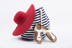 Bright beach accessorize. Red hat and navy bag.