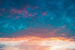 Bright beautiful sunrise at sea. A scenic view of a colorful sky above the ocean. Pink and blue clouds.