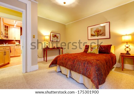 Bright bedroom with beige carpet floor and yellow walls. Red bedding, red frame wall picture and tables accomplish  design