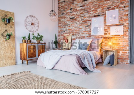 Bright bedroom with double bed, brick wall and rug