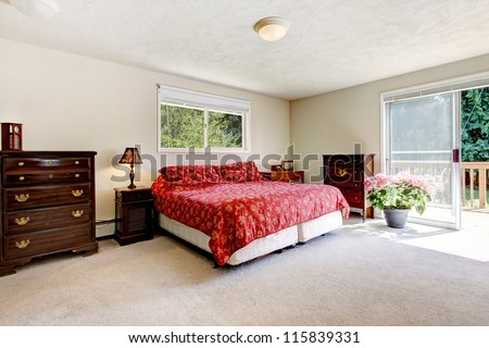 Bright Bedroom with red bed, open balcony door and beige walls. Simple American farm house interior.