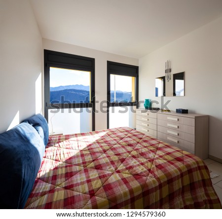 Bright bedroom with window overlooking the mountains. Nobody inside