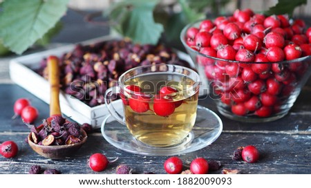 Bright berries of fresh hawthorn with dried berries and tea on a wooden background.Alternative folk medicine using hawthorn. Foto stock ©