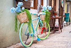 Bright bicycle decorated with baskets of pots with beautiful artificial blue flowers and dense foliage adorns the entrance to souvenir shop or authentic cafe in old town.