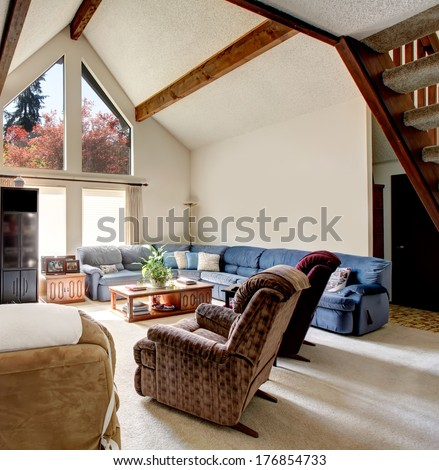 Bright big living room with vaulted ceiling and beams, carpet floor,  rocky wall design. Furnished with comfortable large sofa set, chairs, coffee table and tv