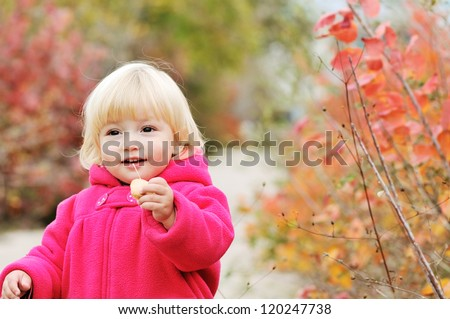 bright blonde baby girl walking in fall park