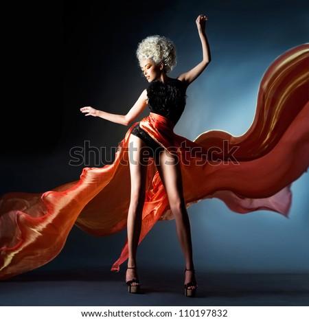 Bright blonde in fluttering red skirt