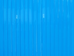 bright blue color corrugated zinc fence, closeup glossy metal plate for surrounding wall of construction site, garage door or roofing, abstract industrial textured background, vertical striped