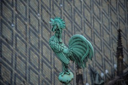 Bright blue-greenish rooster. Crowing copper symbol of St. Vitus. Gothic cathedral roof tiles structure and grey-black symmetric patterns. St. Vitus verdigris patina cock on the crest of the roof.