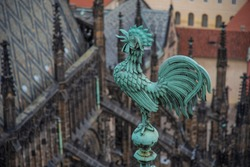 Bright blue-greenish rooster. Crowing copper symbol of St. Vitus. Gothic cathedral spires. Roof tiles structure and grey-black symmetric patterns. St. Vitus verdigris patina cock on roof crest.