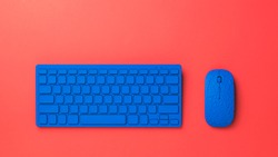 Bright blue keyboard and mouse on a bright red background. Monochrome image of office accessories.