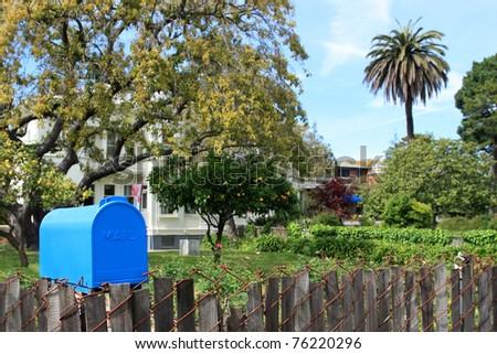 Bright blue mailbox in quiet neighborhood