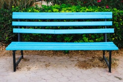 Bright blue painted empty wooden bench in the park for romantic rest during walk, Sliema, Malta, Europe