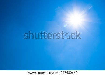 Bright blue sky and sun with flecks of sunlight #247430662