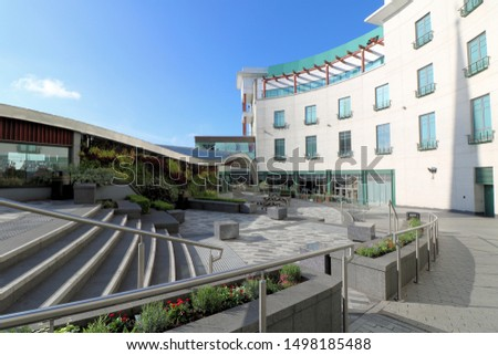 Bright blue sky's over an outdoor seating area surrounded by office exteriors in Birmingham city centre UK. Location of Jamie's Italian restaurant now bankrupt. Commercial Image.