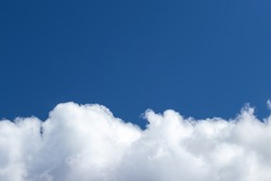 Bright blue sky with cumulus clouds lit by the daytime sun. Abstract background for design.