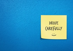 Bright blue wall copy space background with yellow note written with smiley DRIVE CAREFULLY , remind car driver or bike rider to drive carefully with awareness of safety first on the road