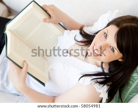 Bright brunette teenager holding a book smiling at the camera in the living room