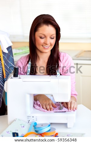 Bright caucasian woman using a sewing-machine in the kitchen at home