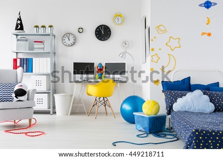 Bright child room with bed, chairs, desk and interesting stickers on the wall