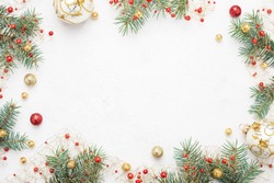 Bright Christmas frame of spruce, red & gold christmas decorations on white background. Copy space. Winter holidays, New Year.