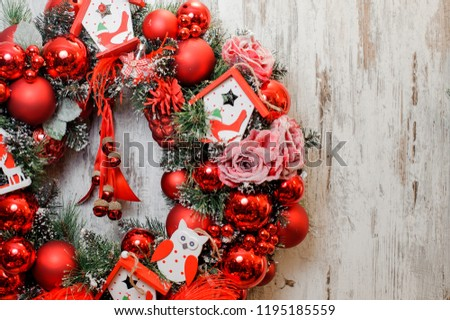 Bright Christmas Wreath decorated with red balls, roses and toy houses on the wooden background #1195185559