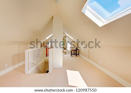 Bright clean attic in the small home with beige carpet.