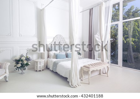 bright, clean stylish interior bedroom and living room with a large panoramic window. beautiful rich antique furniture. four-poster bed, a mirror and a sofa.