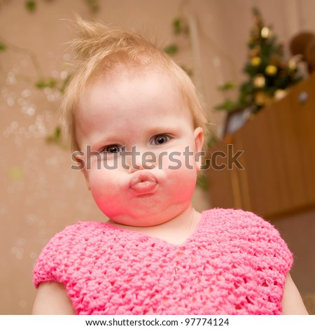 bright closeup portrait of adorable blond baby with blue eyes, with a grimace, and puffed-out cheeks