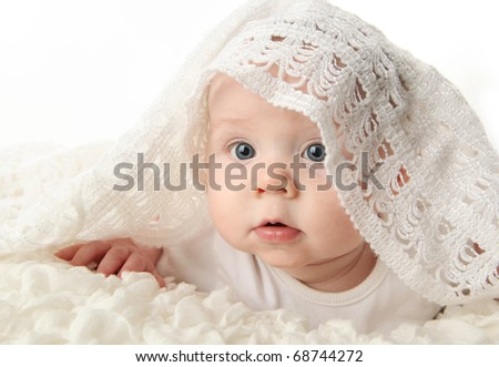 bright closeup portrait of an adorable baby with a white knit blanket draped over head