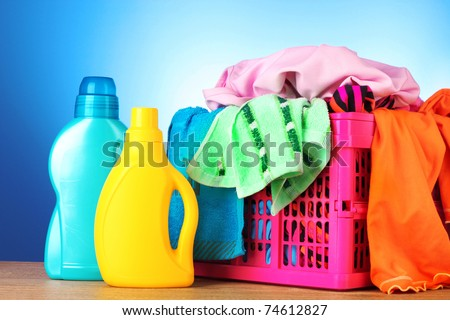 Bright clothes in a laundry basket on blue background