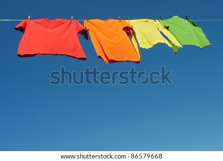 Bright clothes on a laundry line and blue sky with copy space.