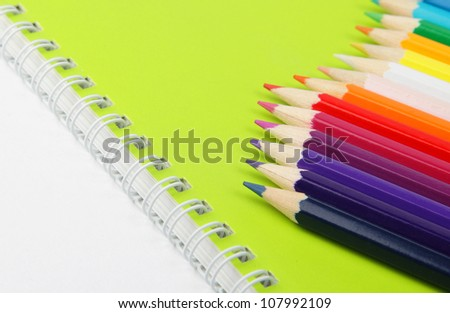 Bright color pencils on green notebook