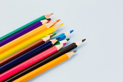 Bright colored assorted pencils on a light blue background. View from above. Place for text.