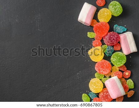 Bright colored candy,a sweets on a dark background, top view #690867805