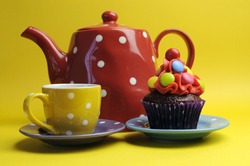Bright colored candy cupcakes for children birthday, Halloween or Christmas party against a cheerful yellow background, with red polka dot tea pot and yellow tea cup.