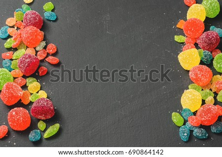 Bright colored candy, sweets, sweets on a dark background, top view #690864142