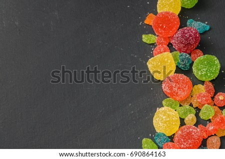 Bright colored candy, sweets, sweets on a dark background, top view #690864163