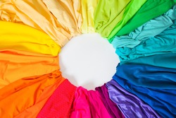 Bright colored fabric flowers laid out on a circle. Material for sewing. Fabric of all colors of the rainbow.