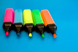 Bright colored markers for highlighting text on a blue background, colored felt-tip pens for drawing.