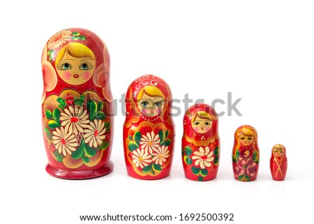 Bright colored nesting dolls on a white background. Russian national souvenir. A row of red nesting dolls of different sizes. Handmade work. Authentic Russian souvenir, hand-painted nesting dolls