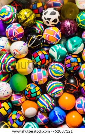 Bright colored, textured bouncy balls behind quartet machine glass