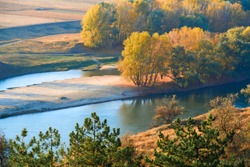 bright colorful autumn forest landscape, trees near river and blue sky, view from high hill