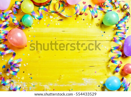 Bright colorful carnival or party frame of balloons, streamers and confetti on a rustic yellow wood table with central copy space for your greeting , invitation or advertising #554433529