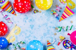 Bright colorful carnival or party scene frame of balloons, streamers and confetti on blue table. Flat lay style, birthday or party greeting card with copy space.