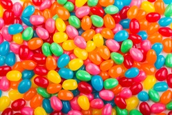 Bright, colorful jellybeans in red, green, pink, blue, yellow and orange colors.