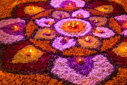 bright colorful mandala of fresh flowers with burning candles at night festival Diwali. rangoli