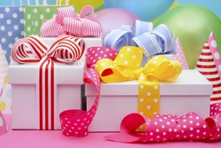 Bright colorful party table with balloons, streamers, party favor gift bags and gifts with bright color ribbons and bows.