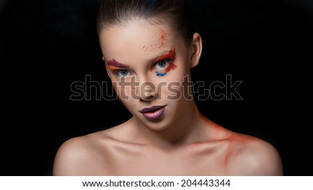 Bright colors on her face, amazing girl. poses in studio on black background