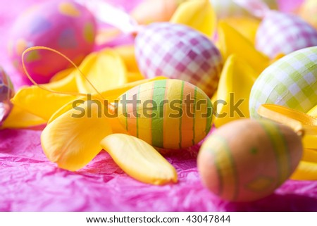 Bright coloured Easter eggs on yellow tulip petals